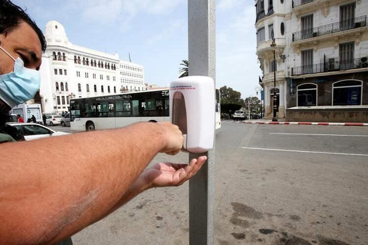 <p>Cezayir'in başkenti Cezayir'de salgını önlemek için sokaklara el dezenfektanları konuldu. Maske takmış bir adam, ellerini temizliyor.</p>