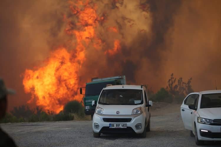 <p>Yol kenarındaki arazözler yoğun duman altında kalmalarına ve yaşadıkları tehlikeye rağmen mücadeleden vazgeçmedi.</p>