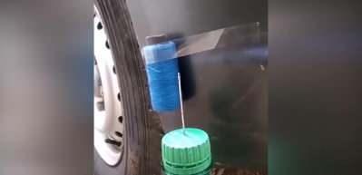 Arabaya bağlı ipliği şişenin ucundaki iğne deliğinden geçirdi!