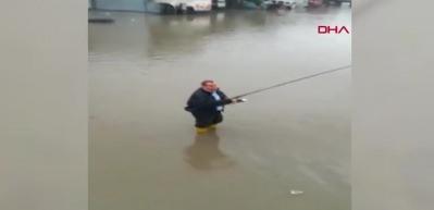 Su taşkınında oltayla balık tutmaya çalıştı