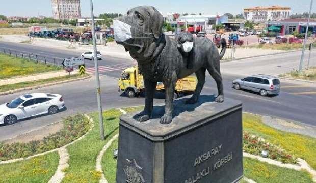 Şehrin simgesi köpek heykeline maske