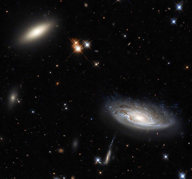 Mientras que la galaxia lenticular se ve en la esquina superior izquierda, la galaxia espiral se ve en la esquina inferior derecha.