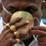 Koronavirüsten korunmak için altın maske takıyor