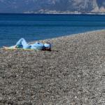Konyaaltı Sahili'nde eşofmanlarıyla güneşlenen turist